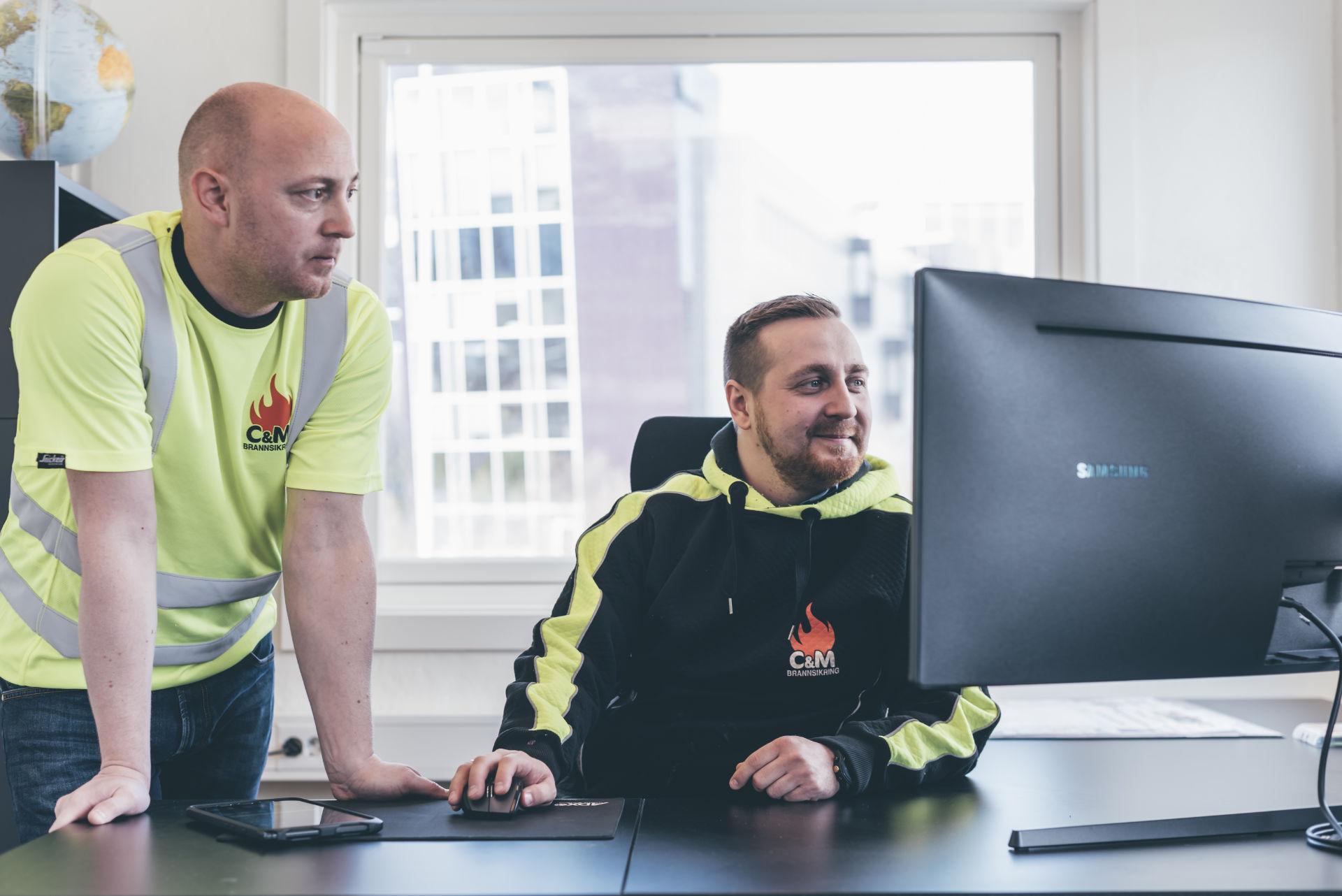 Christer og Michael, står ved datamaskin på kontoret